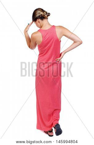back view of standing young beautiful woman. slender woman in a long red dress thoughtfully put a hand to his head.