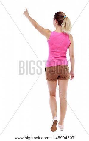 back view of pointing walking woman. going girl pointing. Isolated over white background. Sport blond in brown shorts goes back frame pointing upwards.