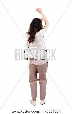 back view of dancing young beautiful woman. Long-haired curly girl swings his arms above his head.