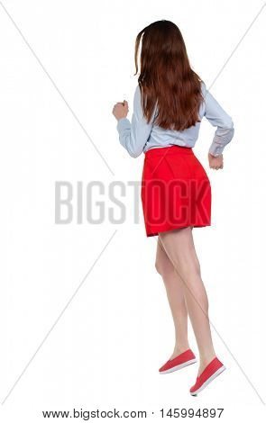 side view of running woman. beautiful girl in motion. Long-haired brunette in red skirt quickly escapes.
