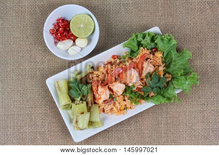 Fried rice with shrimp and grilled green sweet chili with side dish as sliced red hot chili pepper ,halved green lemon and garlic on brown. Top view