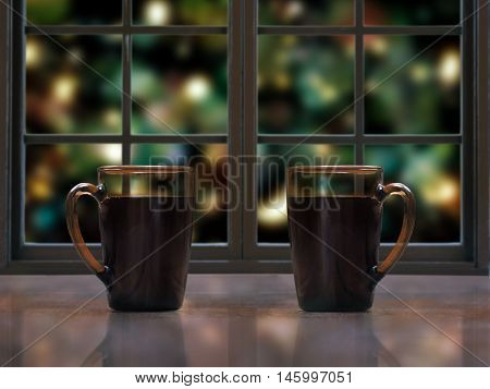 Two mugs with a hot drink - tea or coffee on the window sill of the window. Outside beautiful background blur festive lights