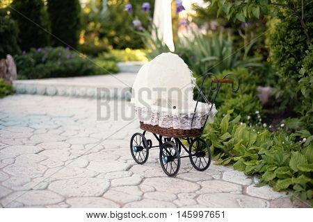 Doll's pram. Vintage doll stroller placed on the stone walkway alley in a beautiful garden with flowers and trees around. Retro cart dolls made of rattan and white lace