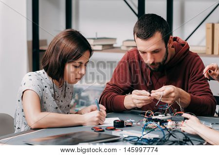 Male and female engineers constructing diy model. Homemade electronics, modern technologies, innovation , science and hobby concept