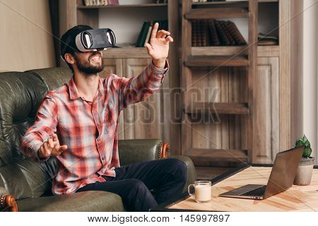 Happy man in vr glasses playing video game. Guy pushing invisible keys and catching something while using virtual reality headset