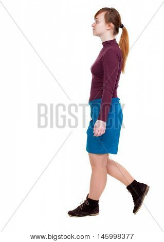 back view of walking woman. beautiful blonde girl in motion. red-haired girl in a blue skirt passes.
