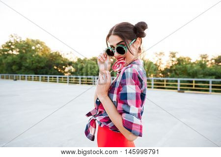 Happy attractive young woman in round sunglasses eating lollipop outdoors