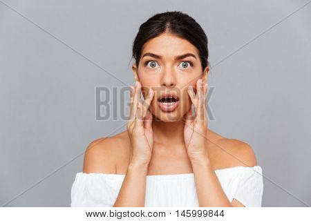 Portrait of shocked pretty young woman touching her face over gray background