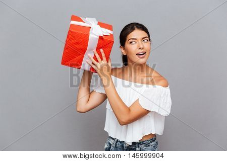 Cheerful young woman wonder what is inside present box isolated on a gray background