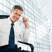 Smiling satisfied businessman looking at camera sit in his chair at office