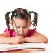 Absorbed little girl drawing with pencils isolated on white background