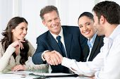 pic of handshake  - Mature businessman shaking hands to seal a deal with his partner and colleagues in a modern office - JPG