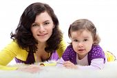 Happy mother in colored clothes with laughing little daughter on white fluffy fur, focus on daughter poster