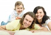 Happy young family - mother and father lie on a white fluffy fur and daughter lie on father and laugh poster