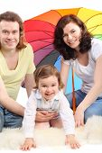 Happy young family - mother, father and little daughter - are sitting under colored umbrella on a white fluffy fur, father embraces daughter poster