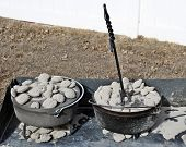 stock photo of dutch oven  - Aluminum and Cast Iron Dutch Ovens along with a lid lifter - JPG