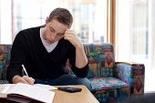stock photo of midterm  - A young college student cramming before his final exams - JPG