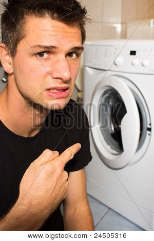Young man unhappy with washing mashine and pointing at it