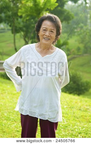 80's Asian senior woman back pain after exercise in the park at morning