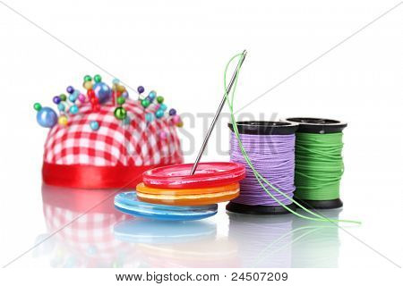 Bright sewing buttons, needle and skeins of thread isolated on white