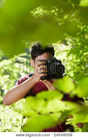 Joven fotógrafo hombre Senderismo en el bosque