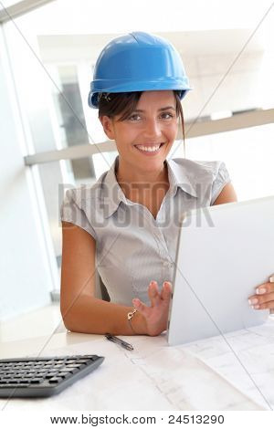 Smiling woman architect in office working with electronic tablet