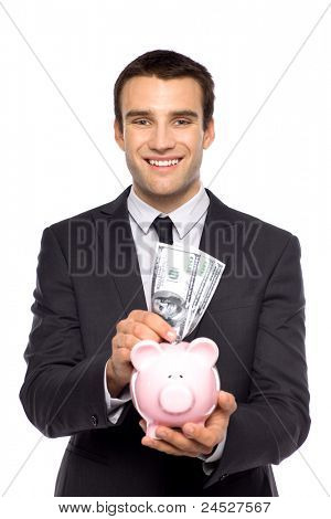 Businessman putting money in piggy bank