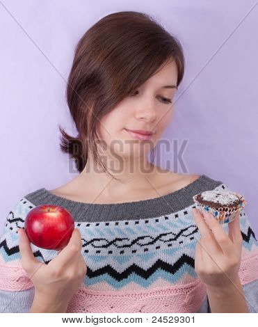 Girl Choosing Between Apple And Cupcake