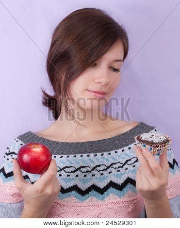 Girl Choosing Between Apple And Cupcake
