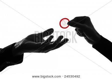one caucasian couple man and woman hands holding tossing offering giving condom  in studio silhouette isolated on white background