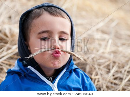 Boy In Haystack With Toy Moustaches
