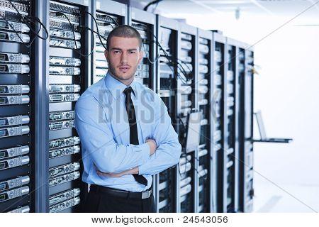 Engenheiro de homem jovem bonito negócios na sala do servidor de datacenter