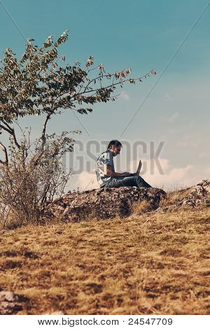 Young Man Using Laptop Sitting On A Hill Against The Blue Sky