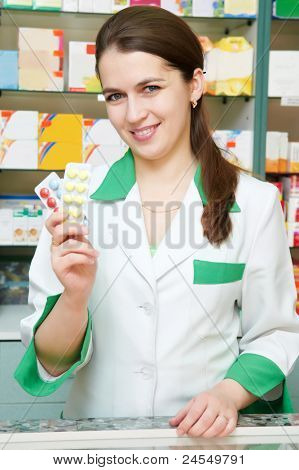 Happy cheerful pharmacist chemist woman standing in pharmacy drugstore with pills