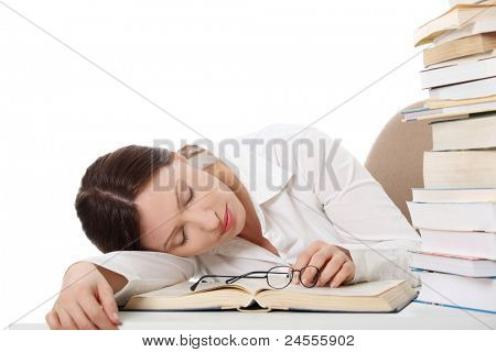 Pretty caucasian girl sleeping on her book near pile of books