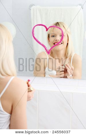 Young beautiful woman drawing big heart on mirror in bathroom.