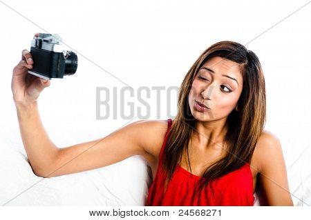 Young Asian Indian girl with old camera, taking photos of herself, winking to her camera