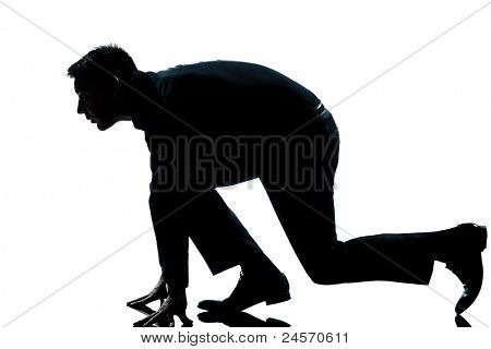 one caucasian man in starting block posture ready to run full length silhouette in studio isolated white background