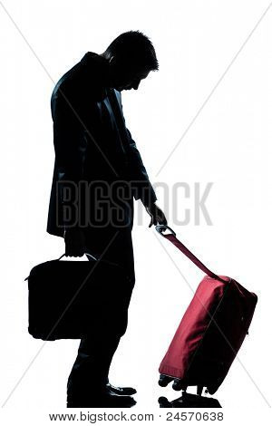side view one caucasian business traveler man tired with suitcase  full length silhouette in studio isolated white background