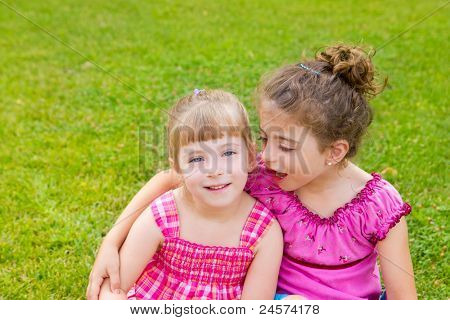 children girls hug in green grass park with pink dress
