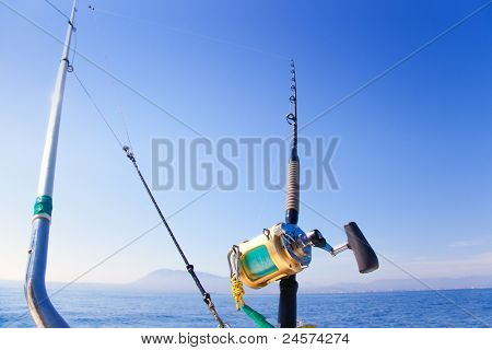 fishing boat trolling with outrigger gear and golden reel rod