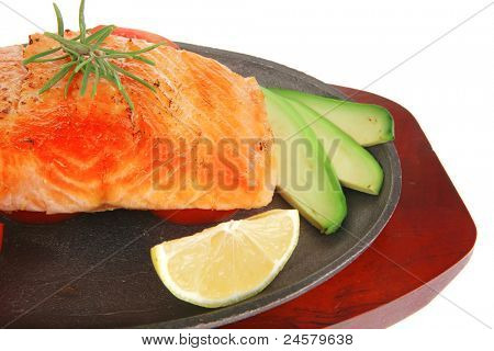 food: hot baked salmon piece served on iron pan over wooden plate isolated on white background