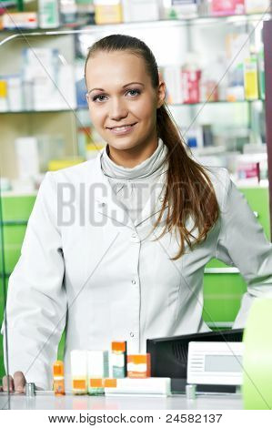 cheerful pharmacist chemist woman standing at cashdesk in pharmacy drugstore