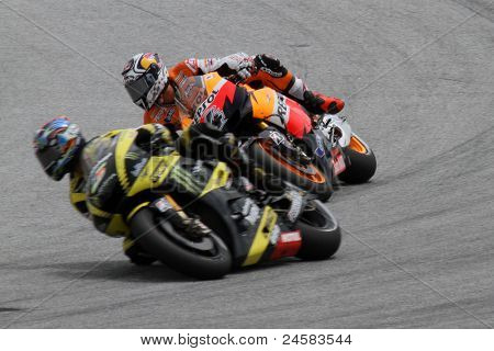 SEPANG, MALAYSIA - OCTOBER 22: MotoGP rider Andrea Dovizioso (4) chases Colin Edwards during the Shell Advance Malaysian Motorcycle Grand Prix 2011 qualifying on October 22, 2011 at Sepang, Malaysia.
