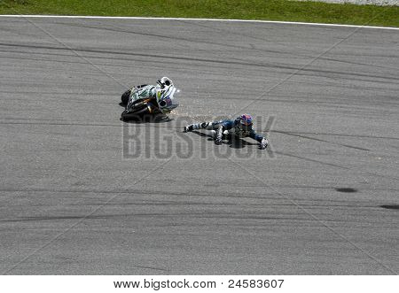 SEPANG, MALAYSIA - OCTOBER 23: Moto2 rider Anthony West falls at turn 15 during warm-up at the Shell Advance Malaysian Motorcycle Grand Prix 2011 on October 23, 2011 at Sepang, Malaysia.