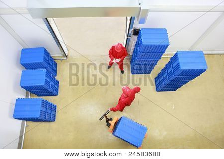 goods delivery in storehouse - overhead view of two workers working in small warehouse