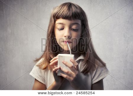 Little girl drinking fruit juice
