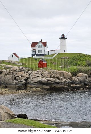White lighthouse and home sitting on rocky bluff