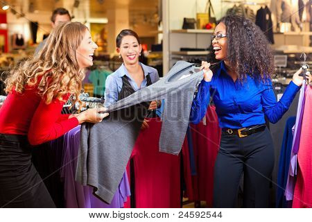 Three women in a shopping mall downtown looking for clothes
