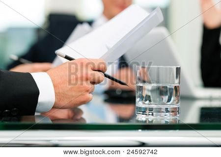 Business - meeting in an office; lawyers or attorneys (only hands) discussing a document or contract agreement